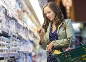 Woman at grocery store reading label on yogurt while holding her shopping basket.