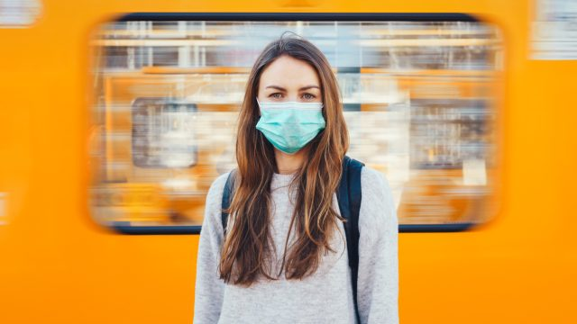 A woman wearing a face mask stands in front of a train that is passing behind her.