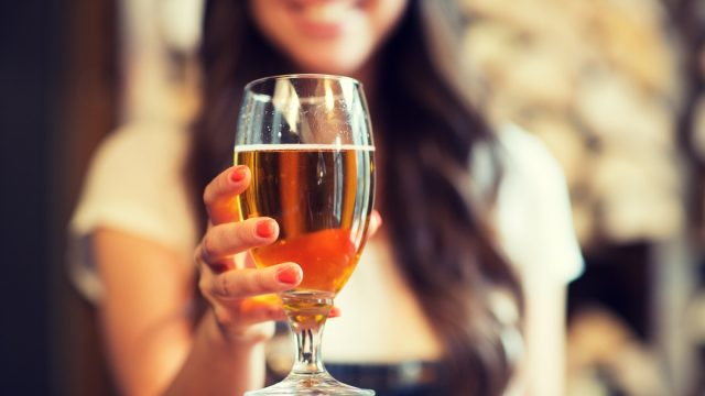 young woman holding a glass of beer