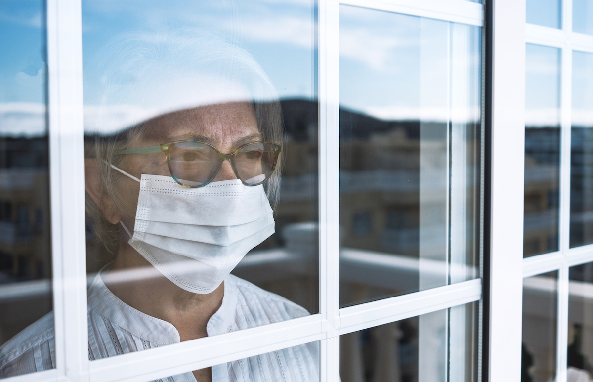 Senior woman in self quarantine to avoid contagion of infection by virus covid-19, stays home looking outdoors from the window