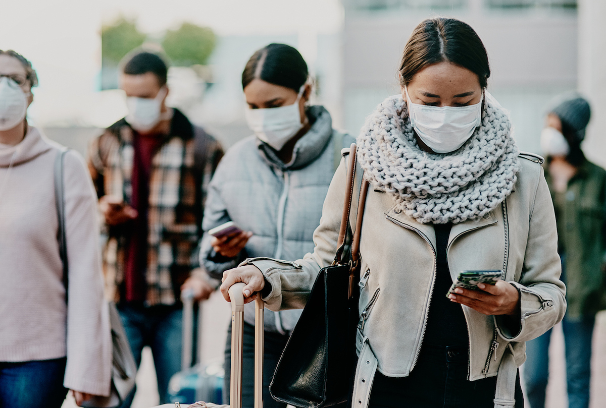 Shot of a young woman using a smartphone and wearing a mask while traveling