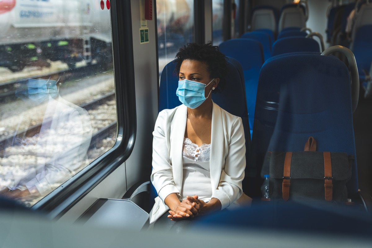 Woman sitting in the train and wearing a protective mask. She is looking trough the window.