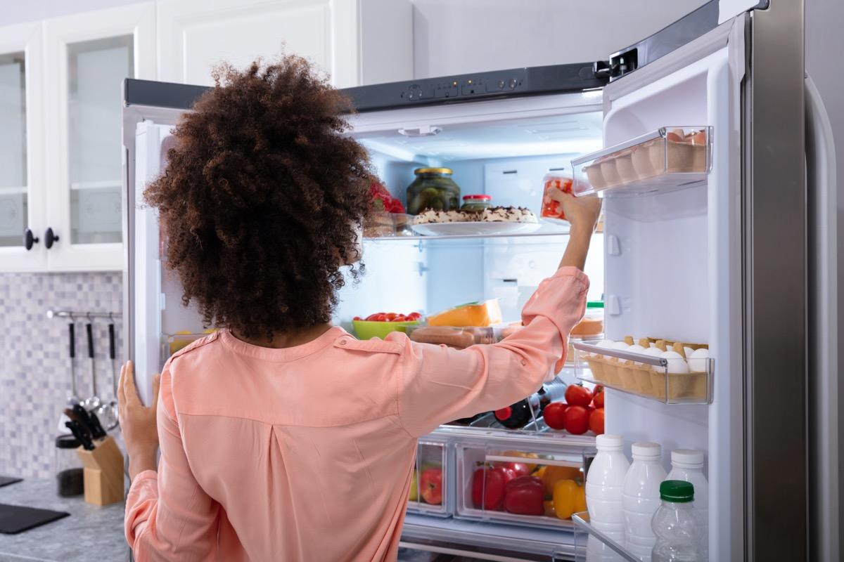 woman in pink shirt with dark curly hair opening double door fridge