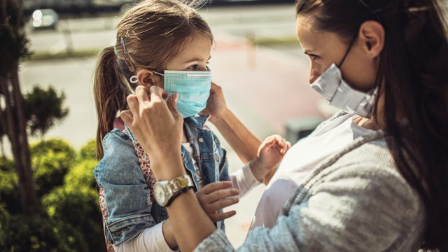 A mother wearing a face masks puts a face mask on her young daughter while they are standing outside