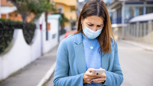 Woman with face protection mask texting on mobile in the street