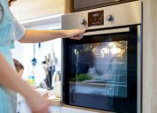 A woman wearing a blue apron turns on the oven in her kitchen