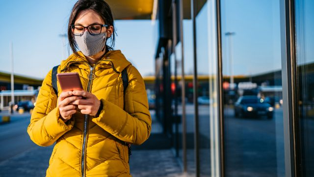 Young woman using smartphone while wearing a mask in time of the COVID pandemic