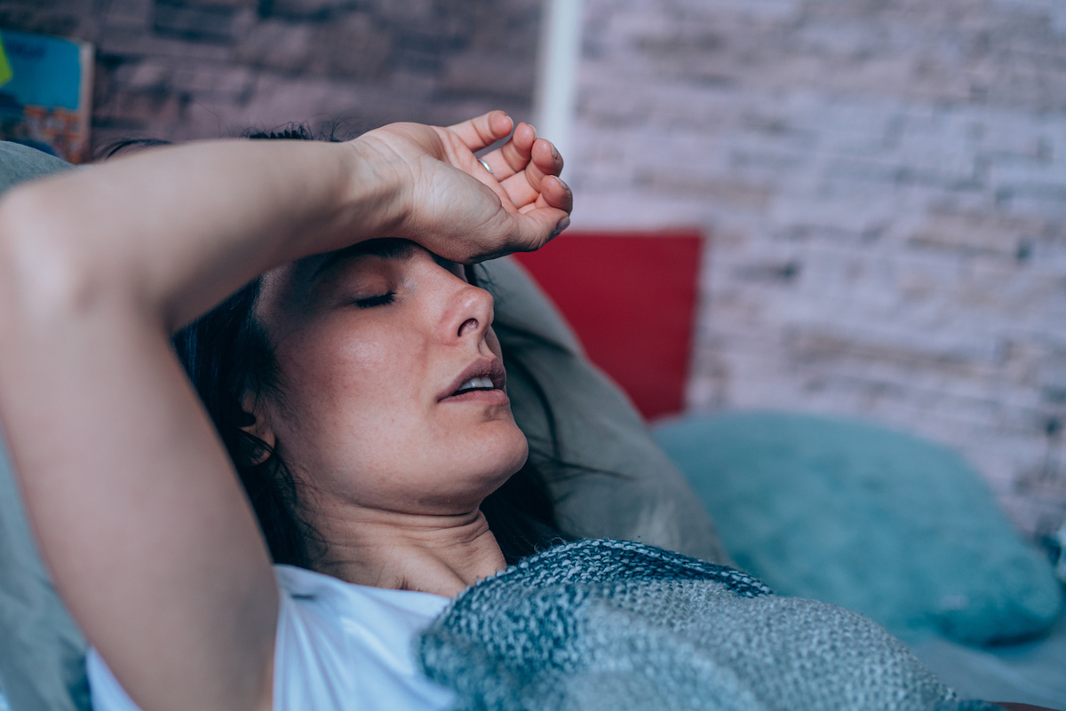 Sick woman lying in the bed covered with blanket with high temperature.