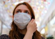 A young woman is considering whether to remove the medical mask after the end of the quarantine due to the coronavirus
