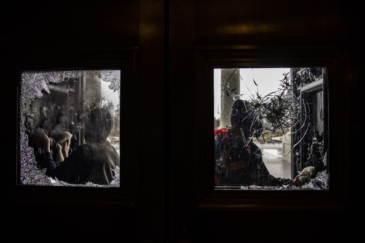 workers clean broken glass on doors at us capitol