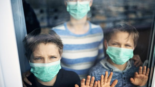Three young kids wearing face masks look out a window.
