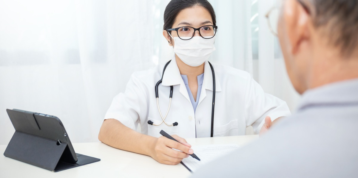 young female doctor wearing glasses and surgical mask talking to older male patient