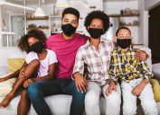 A young family of four wearing face masks while sitting on their couch.