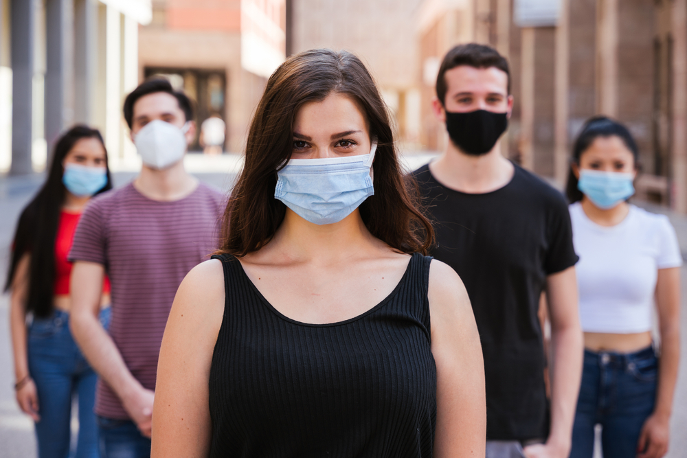 A group of young people wearing face masks stand spread out in an alleyway.