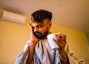 young man with beard holding tea and indicating a headache