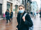 A teenage girl wearing a dark jacket, backpack, and face mask walks down a rainy city street.