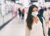 A young woman walks through a train station while wearing a face mask.