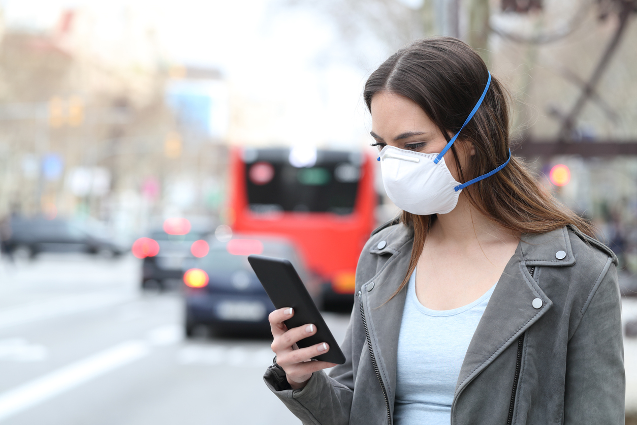 A young woman standing on the sidewalk of a city wearing a face mask checks her smartphone.