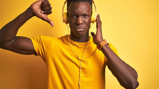 Young man dressed in yellow, listening to music, giving it a thumbs down.