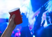 Hand holding a red solo cup at a party