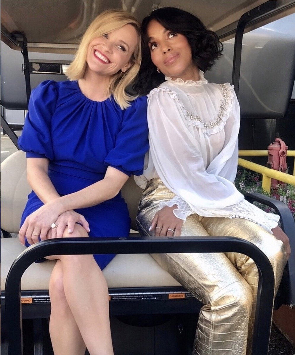 reese witherspoon in a blue dress and kerry washington in gold pants and a white top sitting in the back of a golf cart