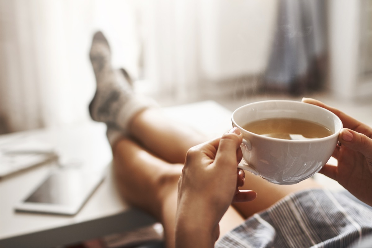 Woman drinking tea with feet up