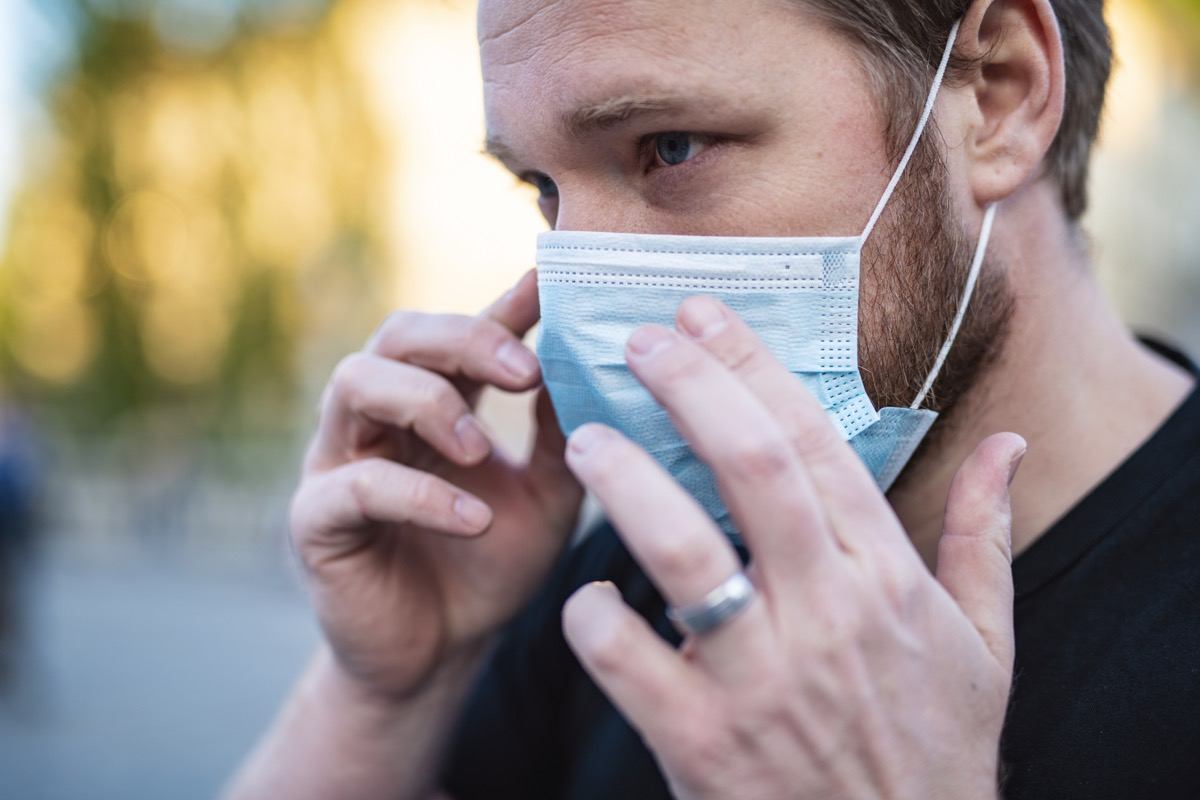 Man Putting On Face Mask In The City To Prevent Getting Coronavirus, COVID-19