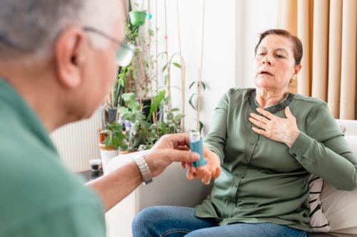 Seorang wanita tua dengan masalah asma menggunakan inhaler asma. Dia berdiri di sofa di rumah sementara suaminya yang sudah lanjut usia membantunya dan membantunya mengatasi masalah kesehatan.Seorang wanita tua dengan masalah asma menggunakan inhaler asma. Dia berdiri di sofa di rumah sementara suaminya yang lebih tua membantunya dan mendukungnya dalam mengatasi masalah kesehatan