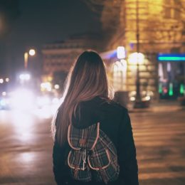 Back view of young woman walking late at night in the city centre