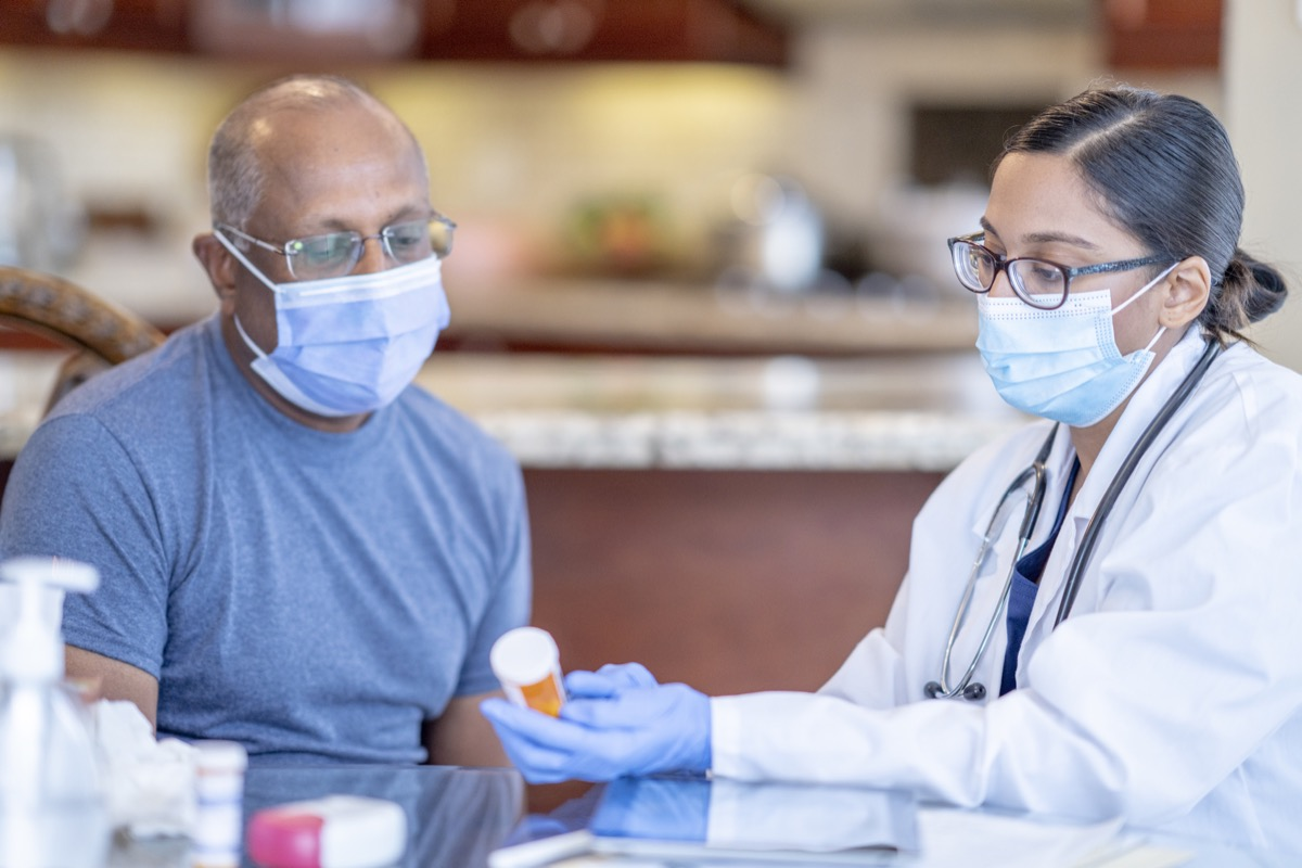 A female doctor is holding a prescription bottle that belongs to her patient. She is reviewing the medicinal ingredients as his patient is seated next to her. Both patient and doctor is using a face mask to help prevent the spread of germs.