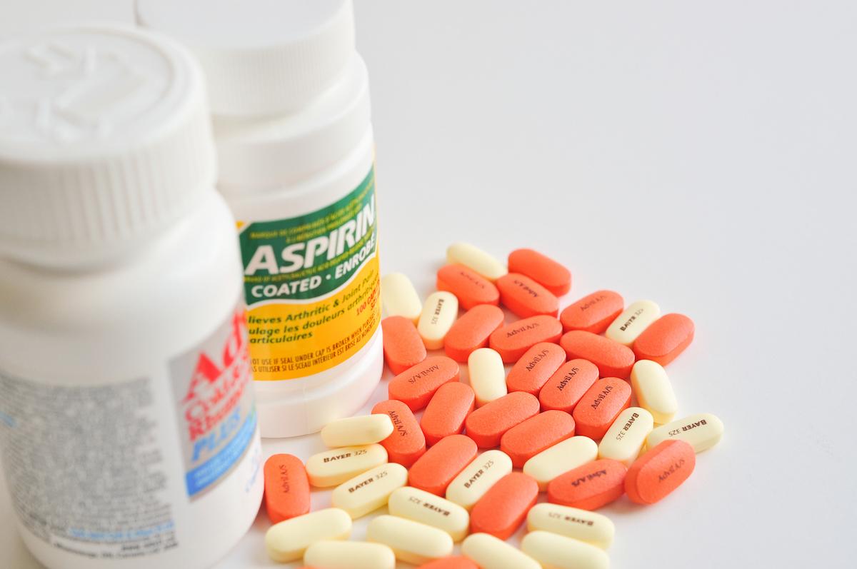 Pills of aspirin and advil on white background