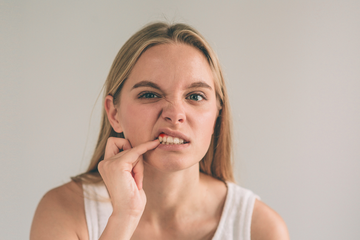 A horizontal photo of a young worried woman looking at her mouth