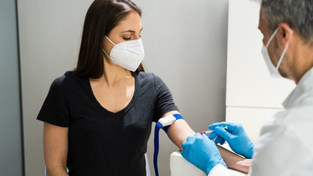woman in mask getting blood drawn by doctor