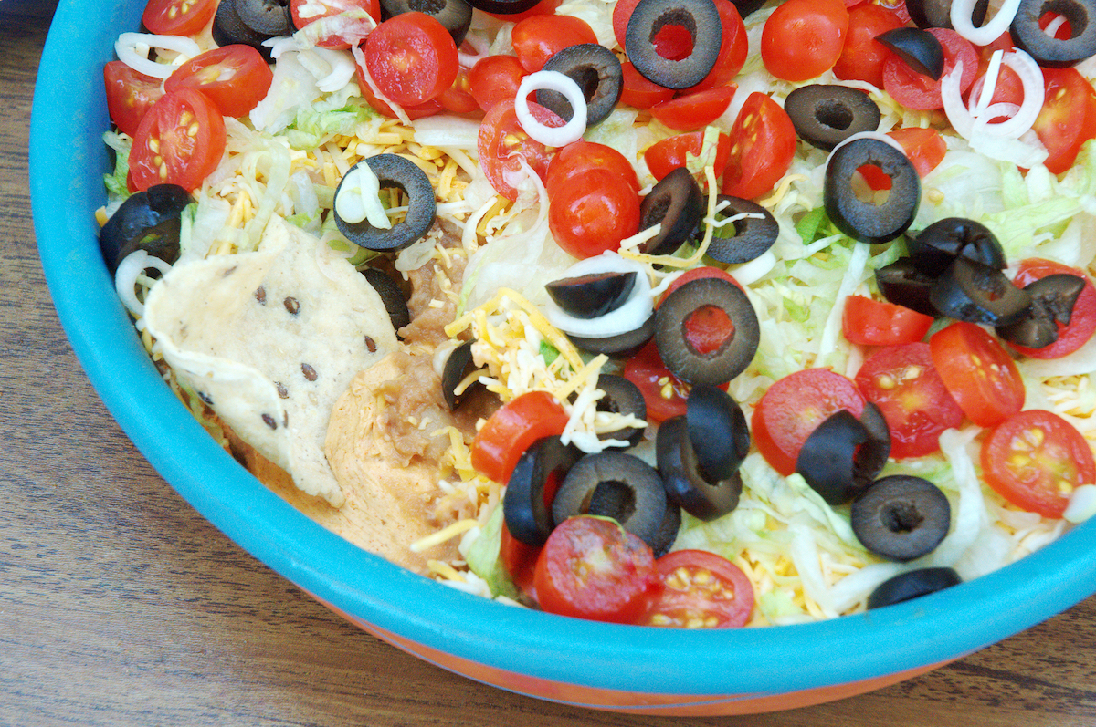 layered taco dip in blue bowl with olives, tomatoes, cheese, lettuce