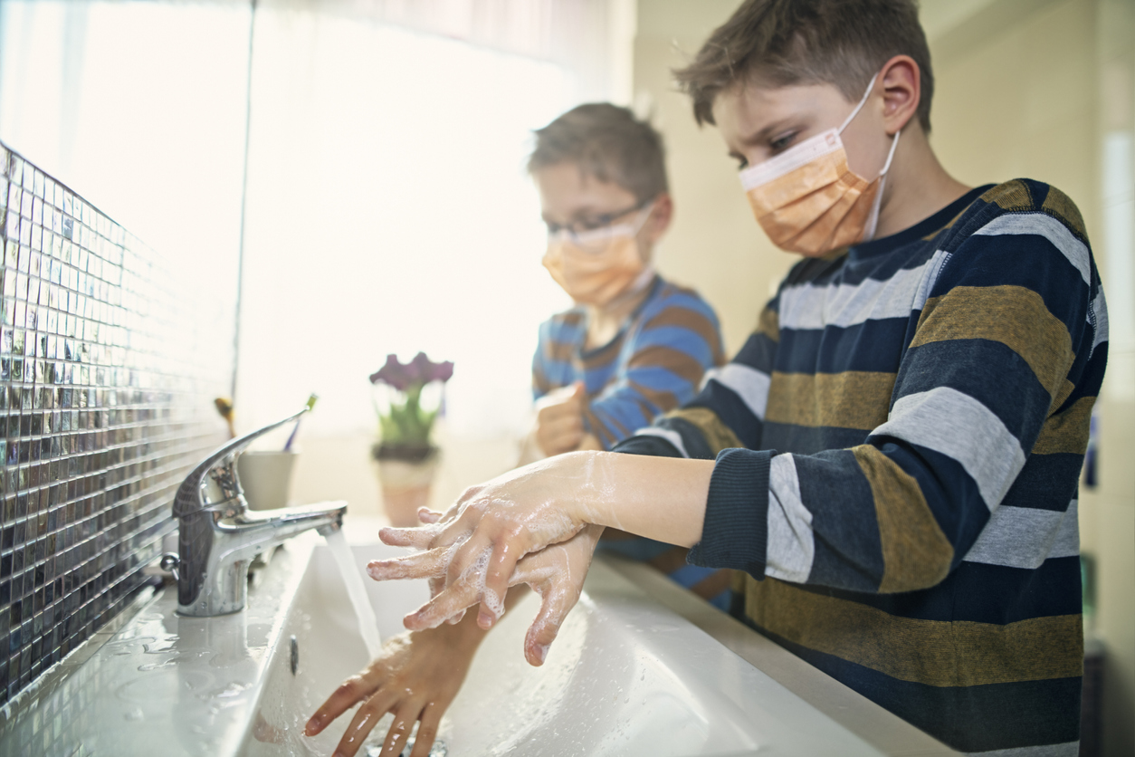 Two young boys wearing face masks wash their hands at a sink.