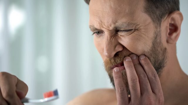 Man brushing teeth and in pain