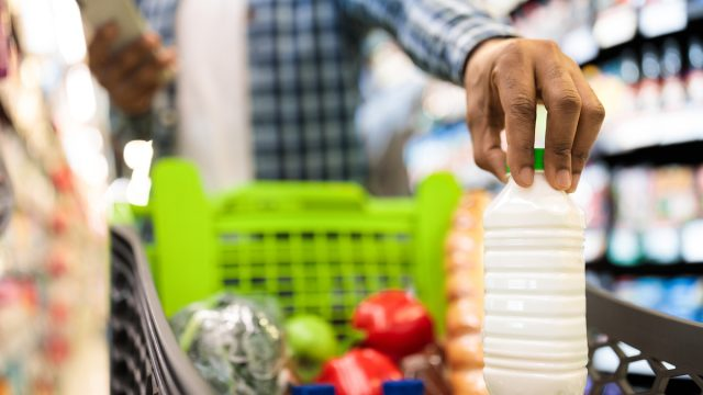 Unrecognizable Guy Doing Grocery Shopping, Putting Products In Cart at Supermarket