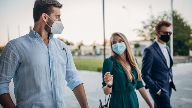 Business people with protective masks walking on the street