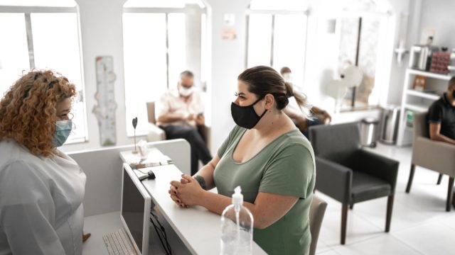 Medical clinic reception, patient waiting in line respecting social distancing using face mask