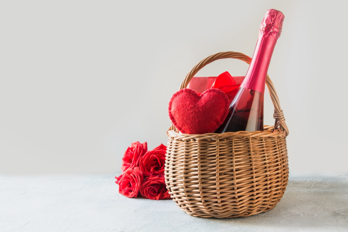 a bottle of champagne and red hart in a basket next to a bouquet of flowers