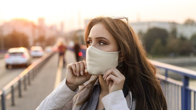 Young woman putting on the mask