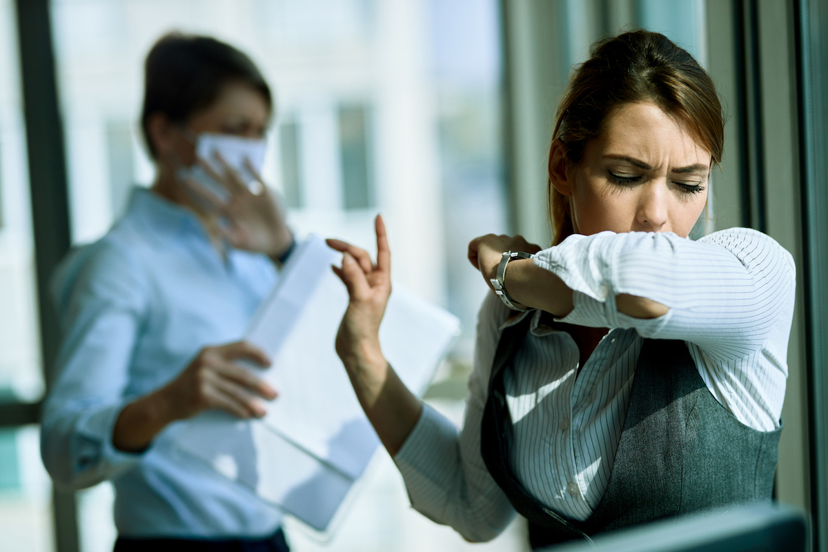 Young businesswoman coughing into elbow in the office. Her coworker is in the background.