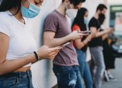 Group of young adult friends standing against a wall, using smart phones and wearing protective face masks.