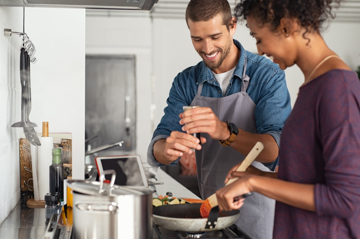young couple making dinner together