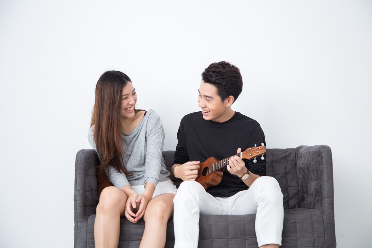 man playing a ukulele on couch next to a woman