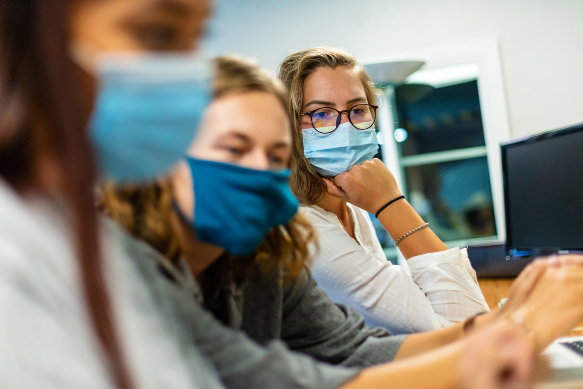 Three female college students; Two in foreground blurred; one in background in focus; wearing face masks using technology working on laptops part of a series (Shot with Canon 5DS 50.6mp photos professionally retouched - Lightroom / Photoshop - original size 5792 x 8688 downsampled as needed for clarity and select focus used for dramatic effect)
