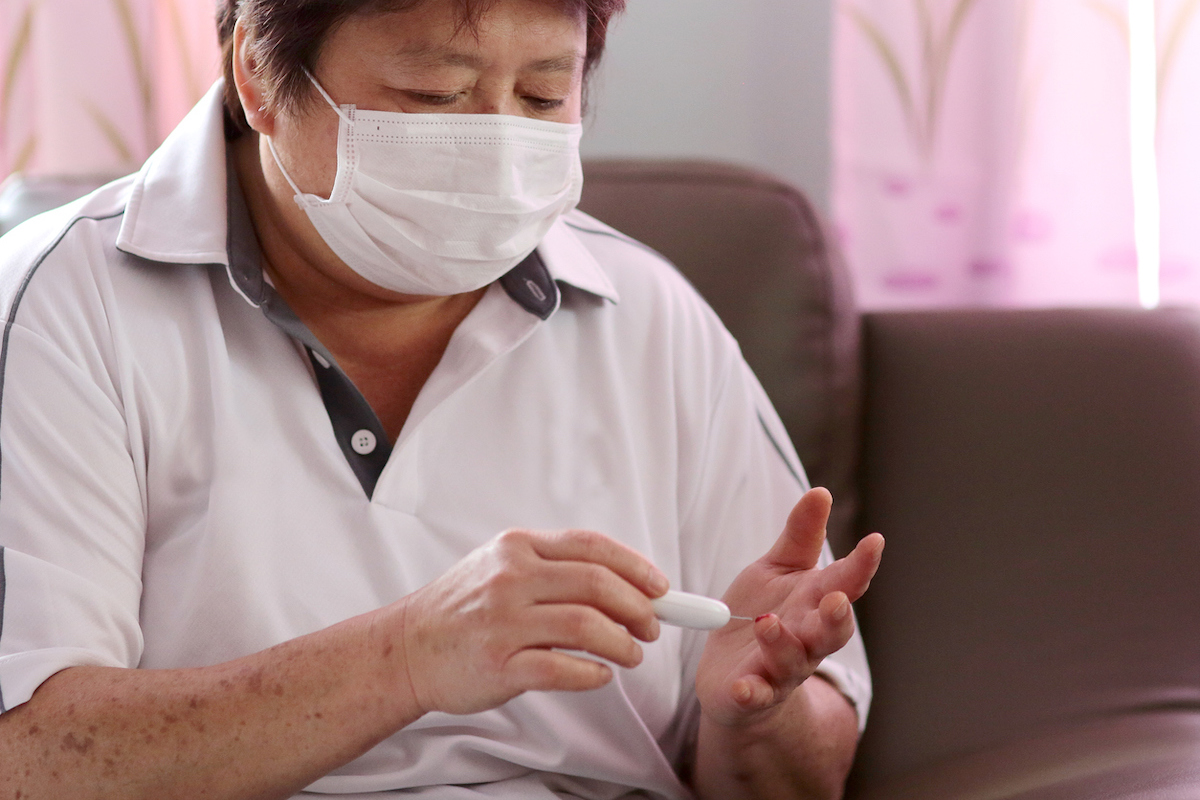 A female adult pricked her finger tips for diabetes blood test.