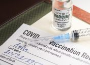 A COVID-19 vaccination record card with a vile of vaccine and a syringe.