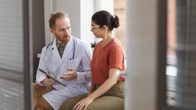 male doctor speaking with a woman patient