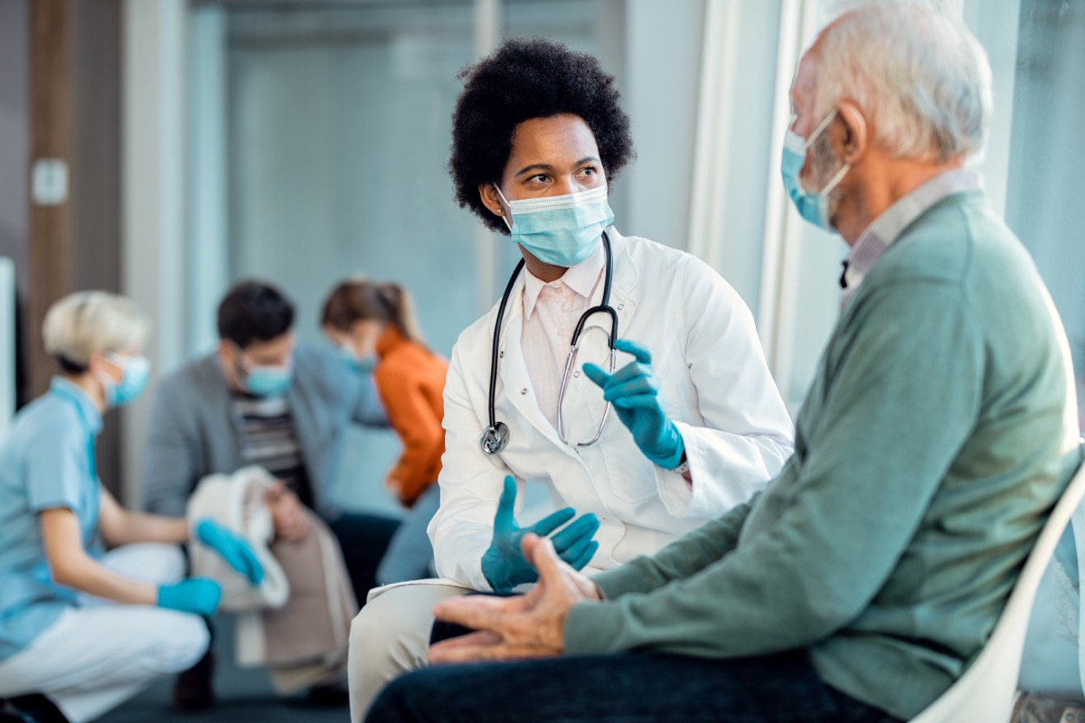 young doctor treating senior male wearing a surgical mask